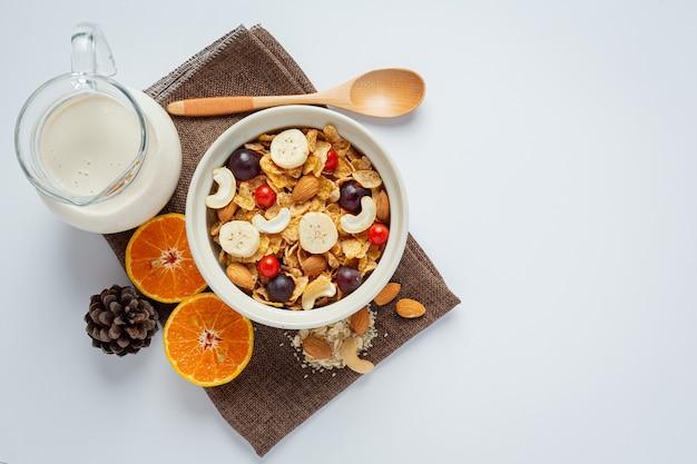 Зерновые в миске и смешанные фрукты на мраморном фоне