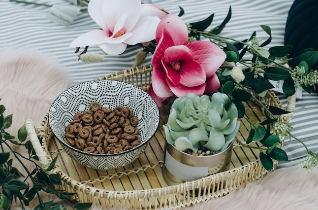 Cereal in a plate flowers in a pot wooden serving tray on blanket at home on bed