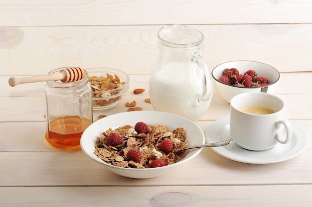 Cereal with raspberries and almonds, milk, honey and coffee healthy breakfast
