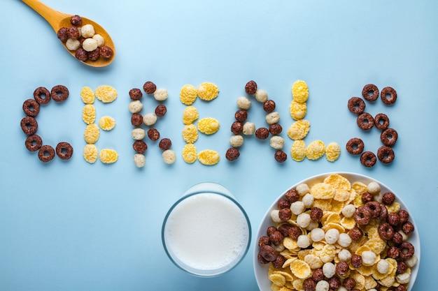シリアルボウル、スプーン、牛乳1杯。健康的なドライブレックファースト用の艶出し、チョコレートボール、リング、コーンフレーク