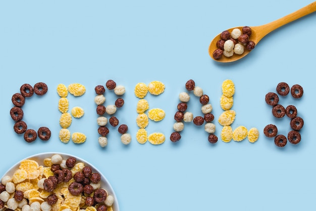 Cereals bowl and spoon on a blue surfce. glazed, chocolate balls, rings and corn flakes for healthy dry breakfast. cereals concept