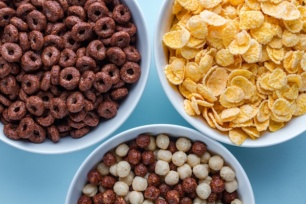 Cereals bowl with chocolate balls, rings and yellow corn flakes for dry breakfast on blue surfce.