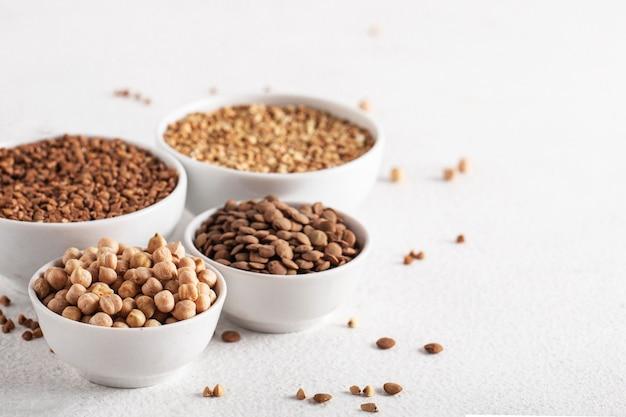 白いテーブルの側面図の穀物そばひよこ豆レンズ豆