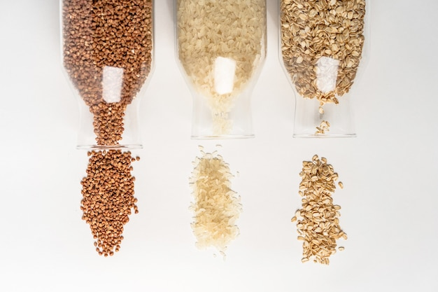 Cereals buckwheat rice oatmeal spilled out of glass containers on a white table