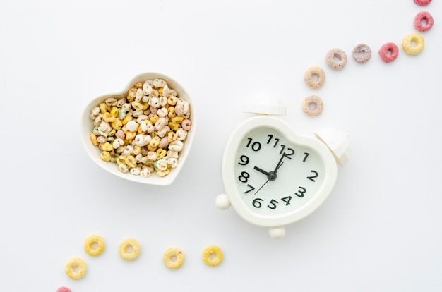 Cereals and clock on white background