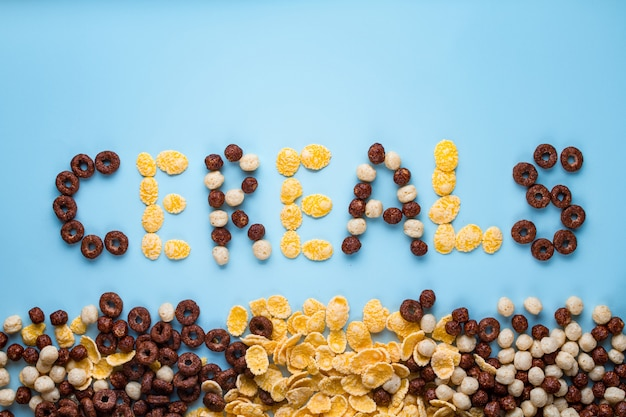 Cereals concept. glazed, chocolate balls, rings and corn flakes for healthy dry breakfast on a blue surfce