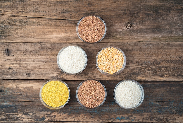 Cereals of different types on a wooden background.