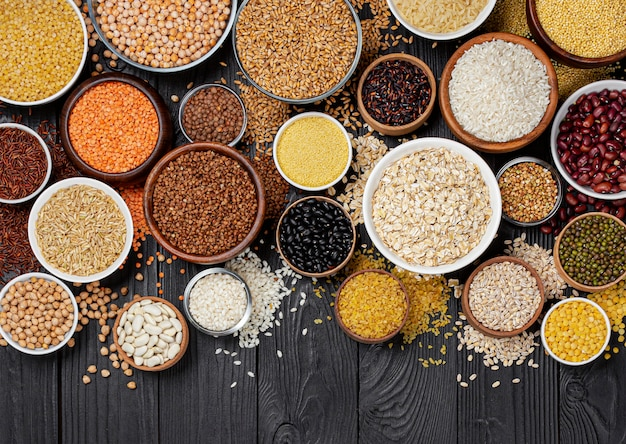 Cereals, grains, seeds and groats black wooden table Premium Photo