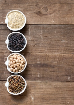 Cereals and legumes in bowls on a wooden table with paper copy space top view