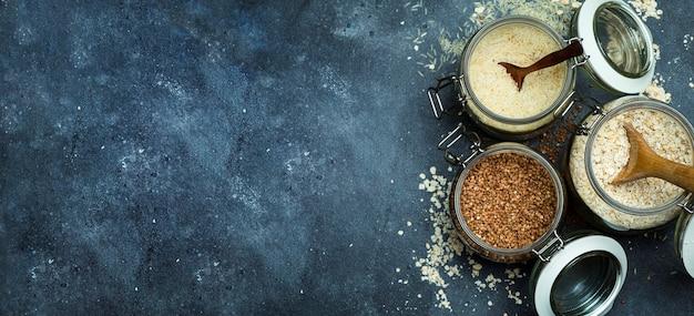 キッチンバナー背景のガラスの瓶に穀物(オートミール、そば、米)。グルテンフリーのコンセプト。健康的な自家製の食品や食事を作るための穀物の品種。
