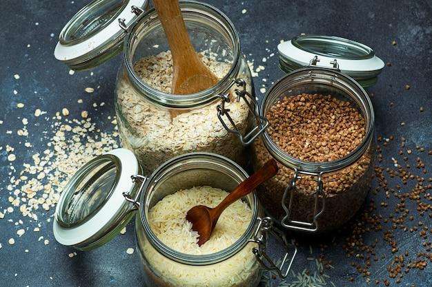 台所のガラスの瓶に穀物(オートミール、ソバ、米)。グルテンフリーのコンセプト。健康的な自家製の食品や食事を作るための穀物の品種。