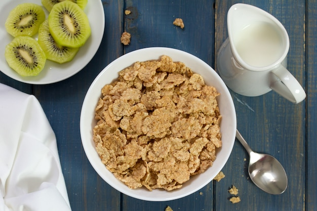 Cereals in white bowl and kiwi