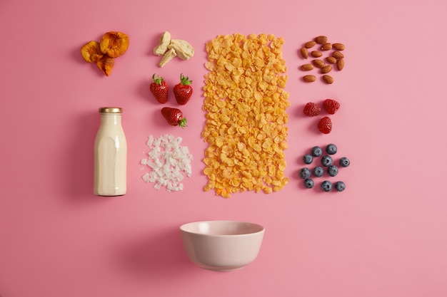 Cereals with dried apples, dates, cashew, pistachio around bottle with milk