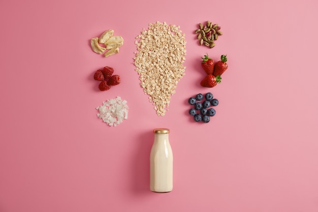 Cereali con mele secche, datteri, anacardi, pistacchi intorno alla bottiglia con latte