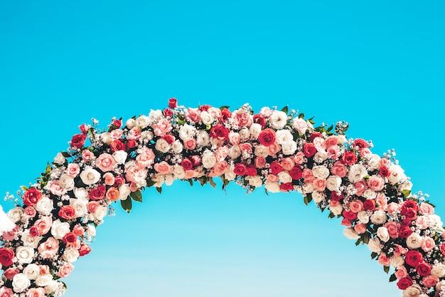 自然の花で飾られたビーチでの儀式の結婚式のアーチ