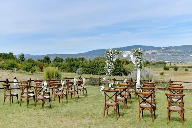 屋外のゲストのための結婚式のアーチ道とキアヴァリの椅子
