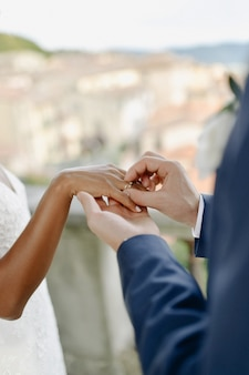 Ceremony of putting the wedding ring on the bride's finger outdoors