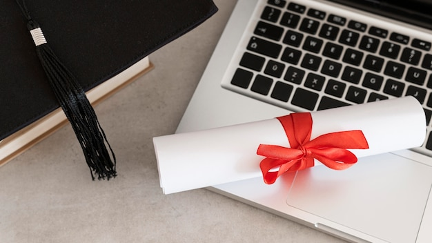 Certificate with ribbon and bow and laptop