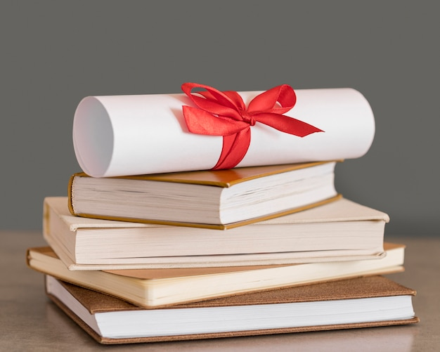 Certificate with ribbon on a pile of books