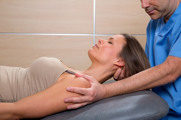 Cervical stretching therapy with therapist in woman neck