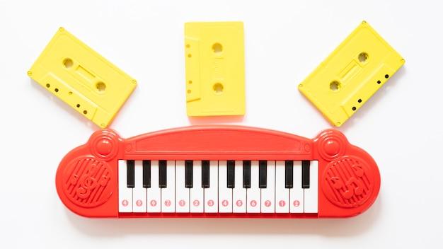 Вид сверху пианино игрушек и cessettes на простой фон