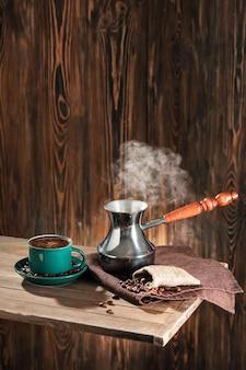 ジェズヴェと木製のテーブルの上のホットコーヒーとカップ