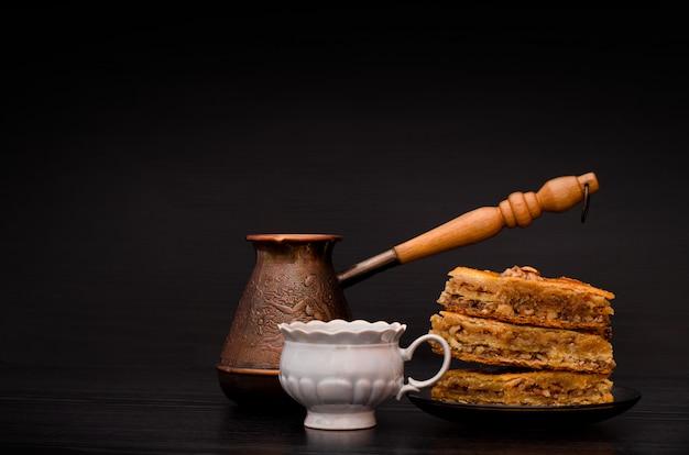 Cezve, coffee mug and a plate of traditional turkish sweet