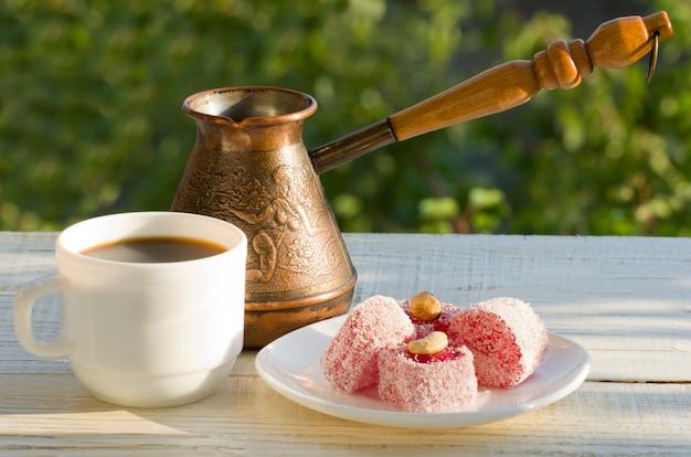 トルコの喜び、コーヒーのマグカップ、緑の心地よい夜の日光の下でのcezve