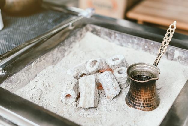 カフェバーで砂の中cezveでトルココーヒーの調製