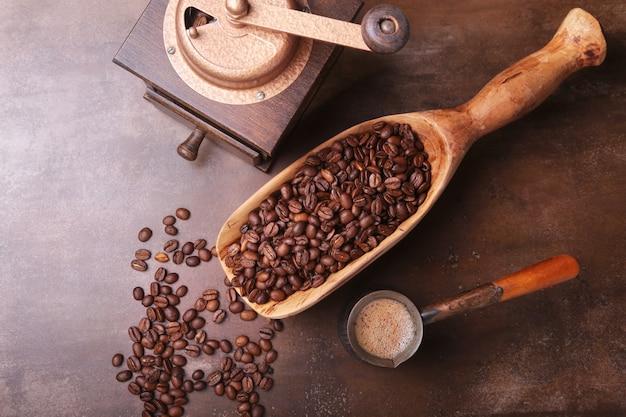 コーヒー豆、コーヒーグラインダー、暗い石のテーブルの上のcezveの古い木製スクープ。