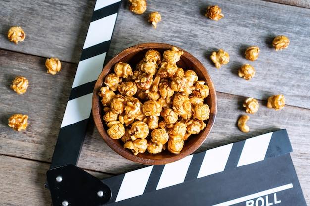 Положение cflat вкусного попкорна и clapperboard карамельки на деревянном столе, взгляд сверху. концепция времени кино