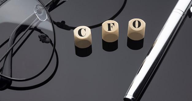 Финансовый директор, написанный на деревянных блоках на черном фоне с ручкой и очками.