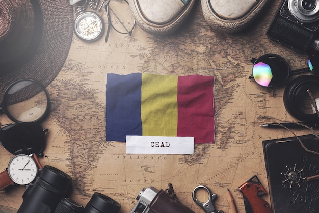 Chad flag between traveler's accessories on old vintage map. overhead shot
