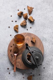 チャガきのこスライスとティーポットで健康的なコーヒーを飲むための準備。トレンディな健康的な注入。
