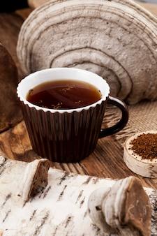 Chaga tea in brown cup. prepared from dried birch mushroom.