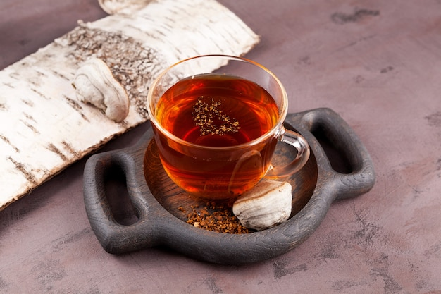 Chaga tea in transparent cup on wooden serving plate. healthy herbal drink.