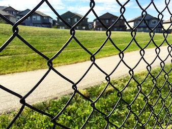 Chain fence on green grass, houses and sky background