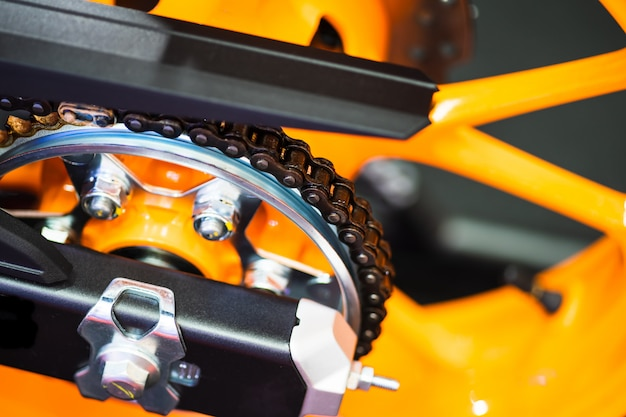Chain and gear wheel of new yellow motocycle close up