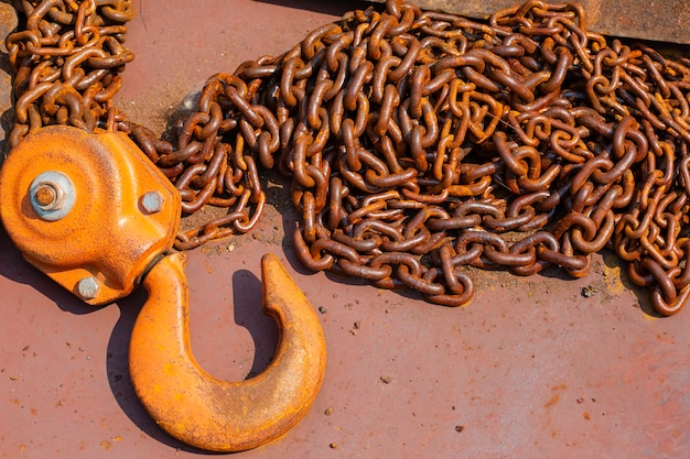 Chain hoist detail of a worn and rusty link in a large chain.