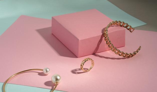 チェーン形の金のブレスレットとコピースペースと緑の紙の背景にピンクのボックスのリング