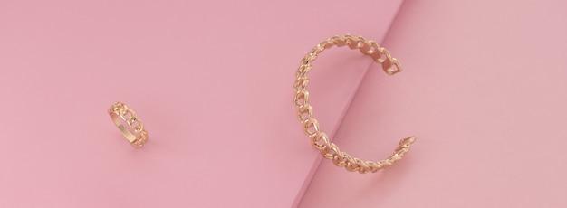 체인 모양의 황금 팔찌와 반지 분홍색 표면에