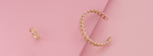 Chain shape golden bracelet and ring on pink surface
