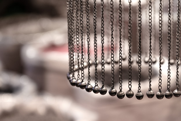 Chains with bells hang in a circle on the background of bags of spices.