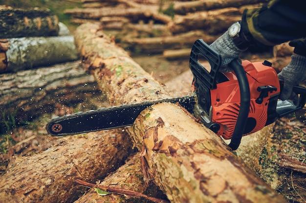 Бензопила. крупный план лесопилки распиловки цепной пилы в движении, опилки летят в стороны. концепция срубить деревья.