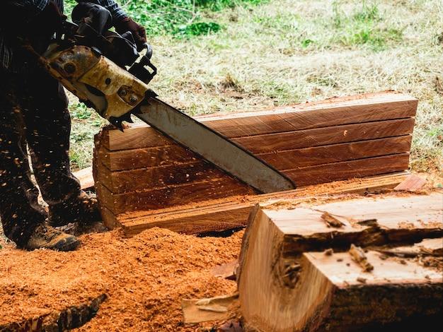 Бензопила в движении по дереву. лесоруб держит старую бензопилу и распиливает бревно, большое дерево в лесу, вокруг летят опилки.
