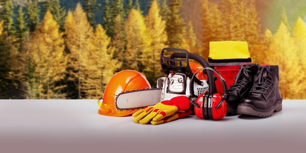 Chainsaw and protective equipment of lumberjack against forest background. banner.