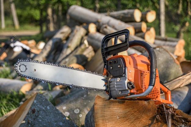 Chainsaw that stands on a heap of firewood in the yard