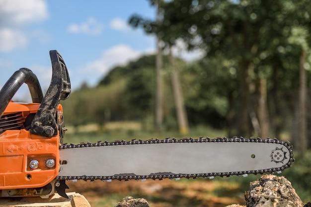 Бензопила, которая стоит на куче дров во дворе на фоне срубленных бензопилой дров и деревьев.