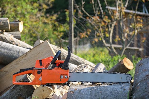 Бензопила, стоящая на куче дров во дворе