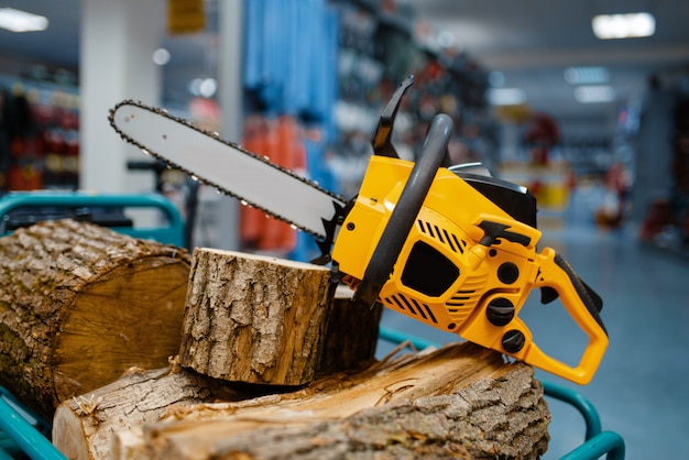 Chainsaw and wooden stump on showcase in power tool store closeup, nobody. choice of equipment in hardware shop, electrical instrument in supermarket